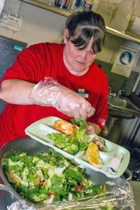 Tina enjoys plating food for the soup kitchen.