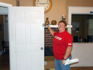 Sharyn proudly displays the door she painted